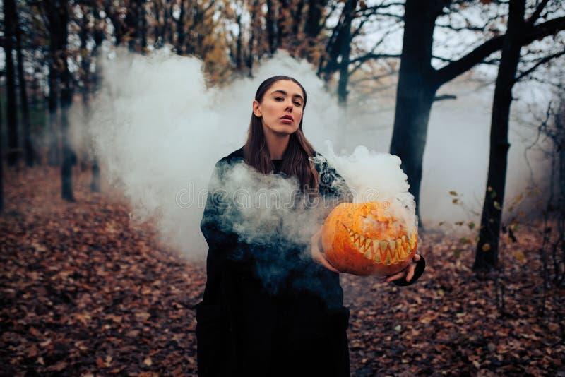 Молодая женщина держа тыкву хеллоуина при белый дым приходя from inside его стоковое фото rf