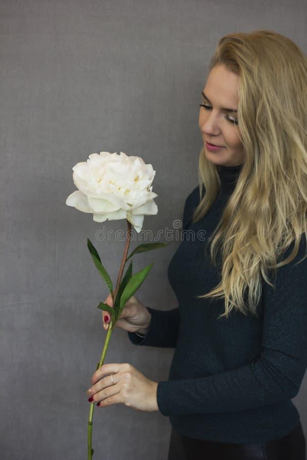 Молодая женщина держит в руках сочный красивый пион стоковое фото rf