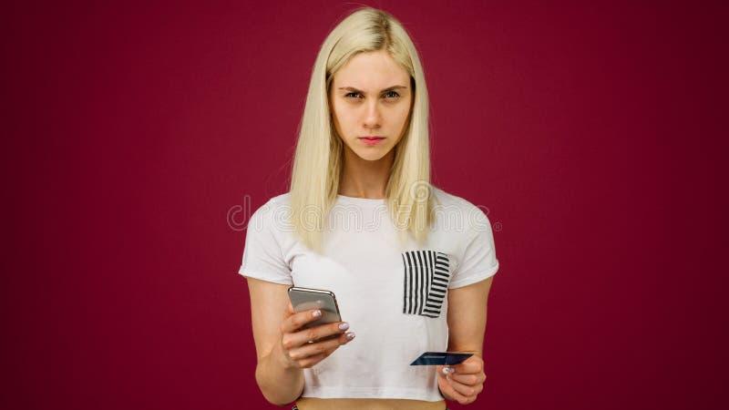Молодая женщина держит смартфон и кредитную карточку в ее руках Проблемы с картой банка, из-за преграждать или неправильно стоковая фотография