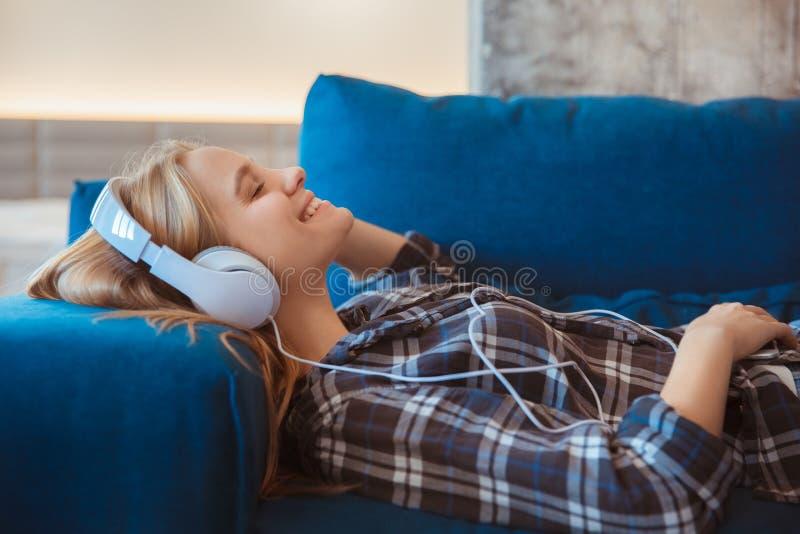 Молодая женщина дома в усмехаться музыки живущей комнаты слушая стоковые изображения rf
