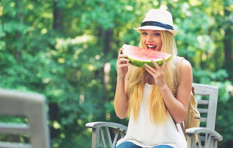 Молодая женщина есть арбуз снаружи стоковые изображения rf
