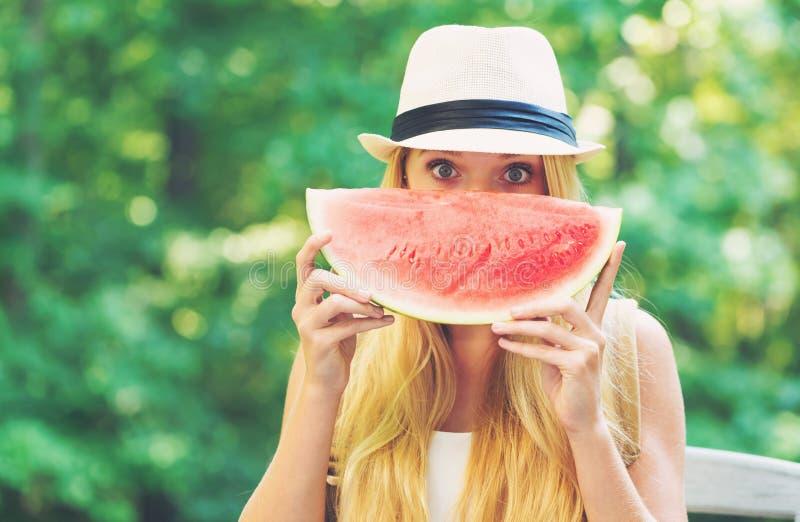 Молодая женщина есть арбуз снаружи стоковое изображение