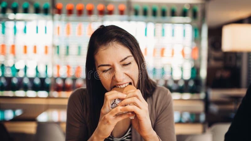 Молодая женщина есть наварный гамбургер Жаждая фаст-фуд Наслаждающся виновным удовольствием, есть высококалорийную вредную пищу У стоковая фотография rf