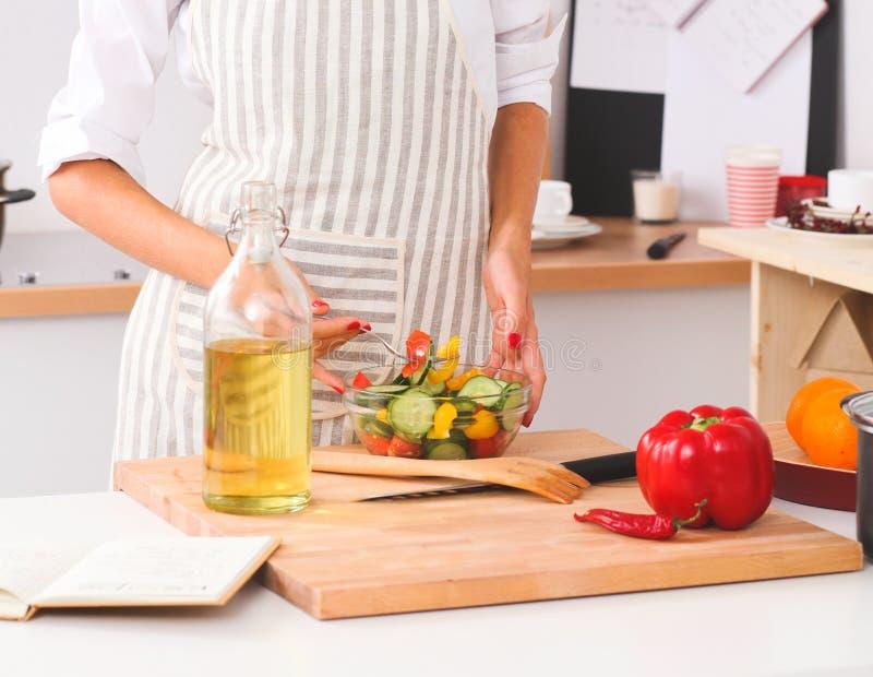 Молодая женщина есть свежий салат в современной кухне стоковая фотография