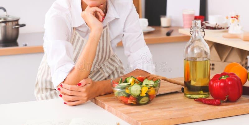 Молодая женщина есть свежий салат в современной кухне стоковые фото