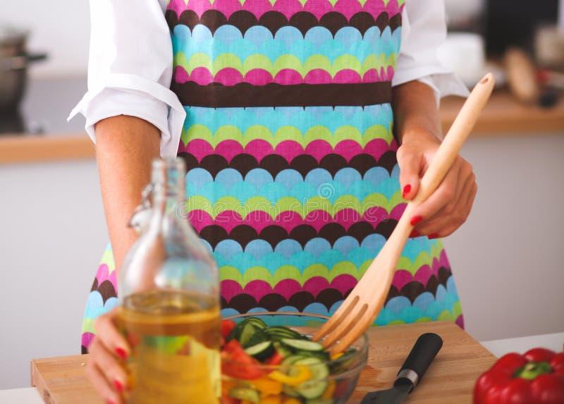 Молодая женщина есть свежий салат в современной кухне стоковые изображения rf