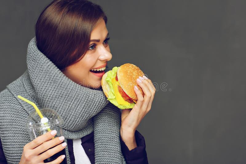 Молодая женщина есть фаст-фуд с потехой изолировано стоковое фото rf