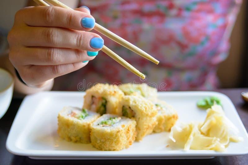 Молодая женщина ест крены суш с палочками стоковая фотография