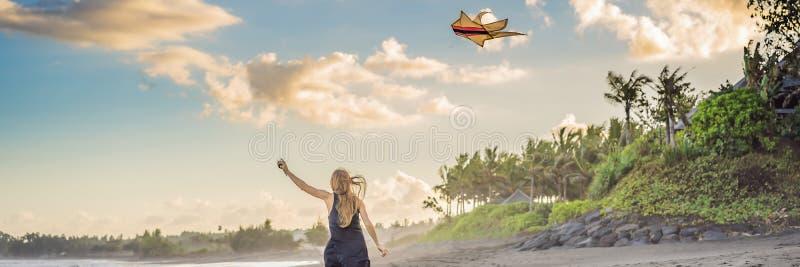Молодая женщина запускает змея на пляже Мечта, устремленности, ЗНАМЯ планов на будущее, ДЛИННЫЙ ФОРМАТ стоковая фотография rf