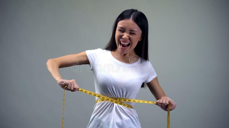 Молодая женщина затягивая измеряя ленту, пытая с диетой, булимия стоковое изображение