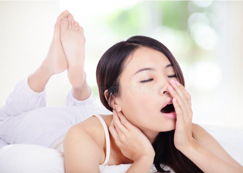 Молодая женщина зевая в кровати в утре стоковая фотография rf