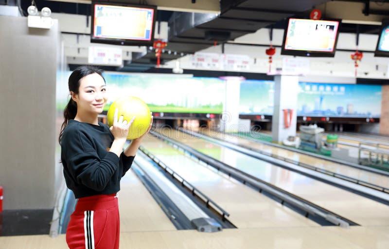 Молодая женщина играет боулинг стоковое изображение rf