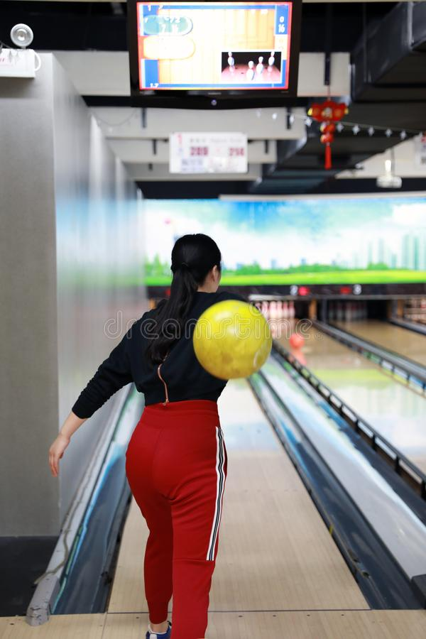Молодая женщина играет боулинг, боулинг Tenpin Взрослый, нерезкость стоковое изображение