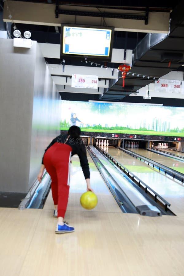 Молодая женщина играет боулинг, боулинг Tenpin Взрослый, нерезкость стоковое фото