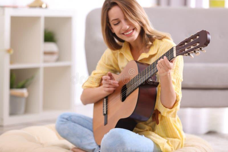 Молодая женщина играя акустическую гитару стоковое изображение