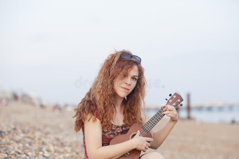 Молодая женщина играя гавайскую гитару стоковое фото
