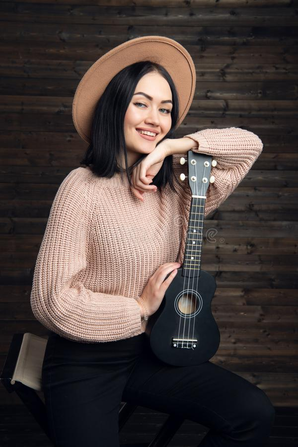 Молодая женщина играя гитару и усмехаться нот иллюстрации электрической гитары принципиальной схемы Домашняя атмосфера на предпос стоковые фото