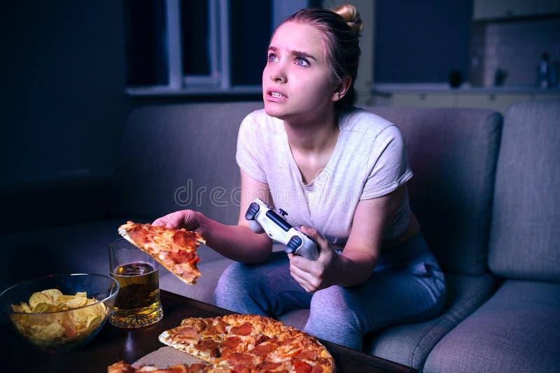 Молодая женщина играя игру вечером Голодная модель смотрит вверх на экране Удержание куска пиццы и gamepad Самостоятельно в темно стоковые изображения rf