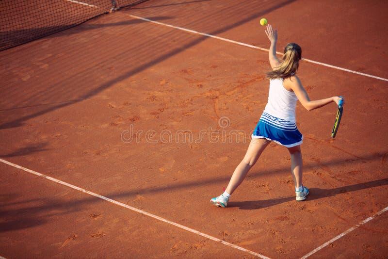 Молодая женщина играя теннис на глине forehand стоковое фото rf