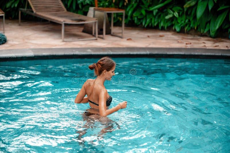 Молодая женщина идет поплавать в бассейне стоковая фотография rf