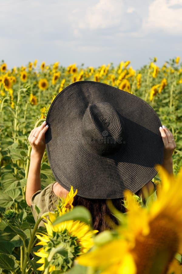 Молодая женщина идя в поле с солнцецветами Красивая маленькая девочка наслаждаясь природой на поле солнцецветов на заходе солнца  стоковые изображения