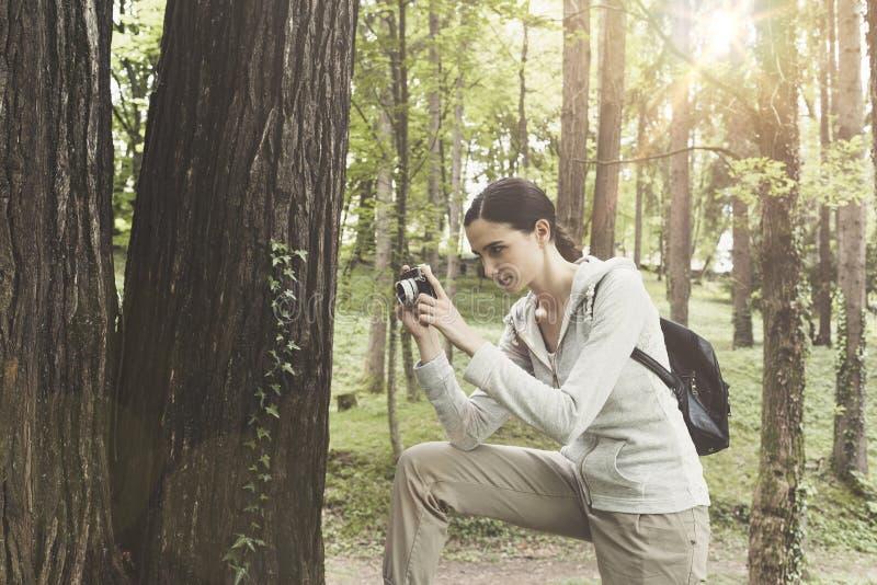 Молодая женщина идя в природу и фотографируя стоковое фото rf