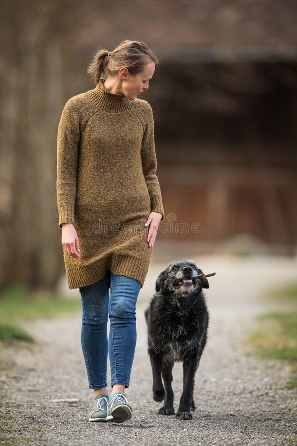Молодая женщина идя ее собака стоковое изображение