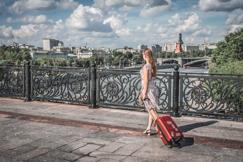 Молодая женщина идя и нося чемодан в Москве стоковая фотография rf