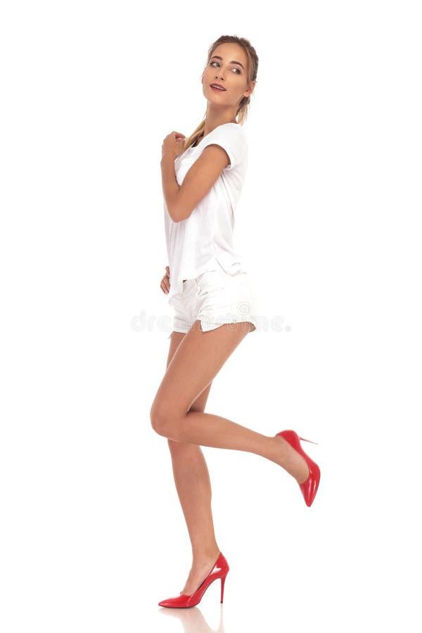 Молодая женщина идя и рассматривая назад ее плечо стоковое изображение rf