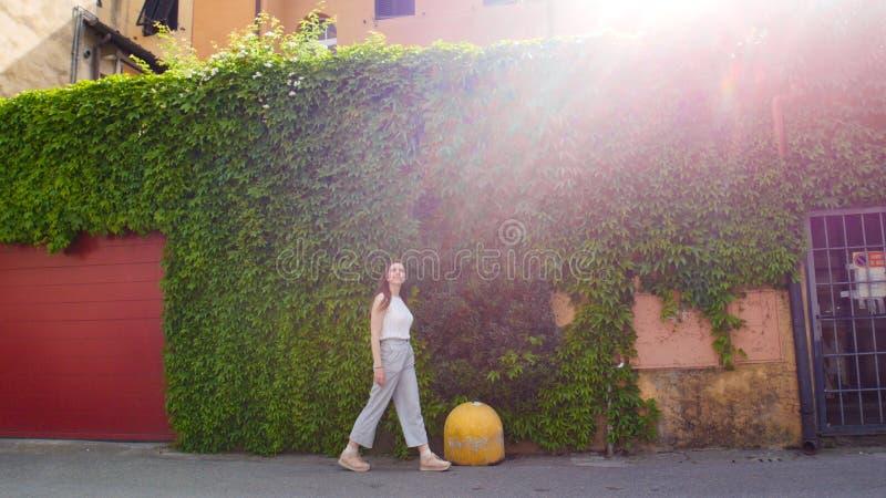 Молодая женщина идя на улицы за светом зеленой стены ярким стоковые изображения rf
