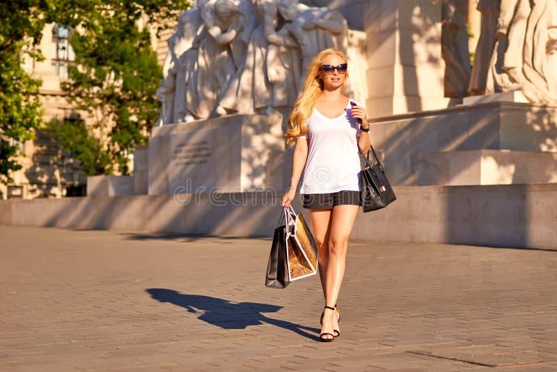 Молодая женщина идя с хозяйственными сумками в заходе солнца стоковые фото