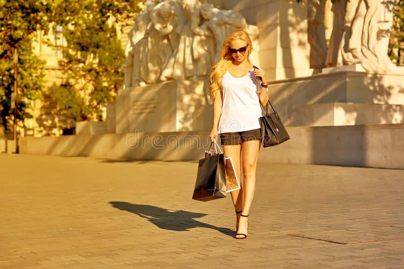 Молодая женщина идя с хозяйственными сумками в заходе солнца стоковое изображение rf
