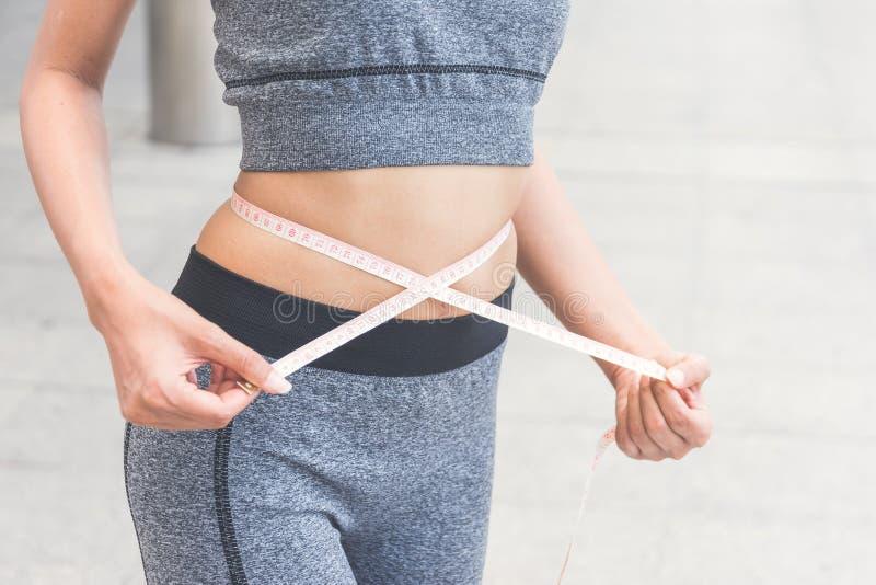 Молодая женщина измеряя ее талию с рулеткой стоковое фото