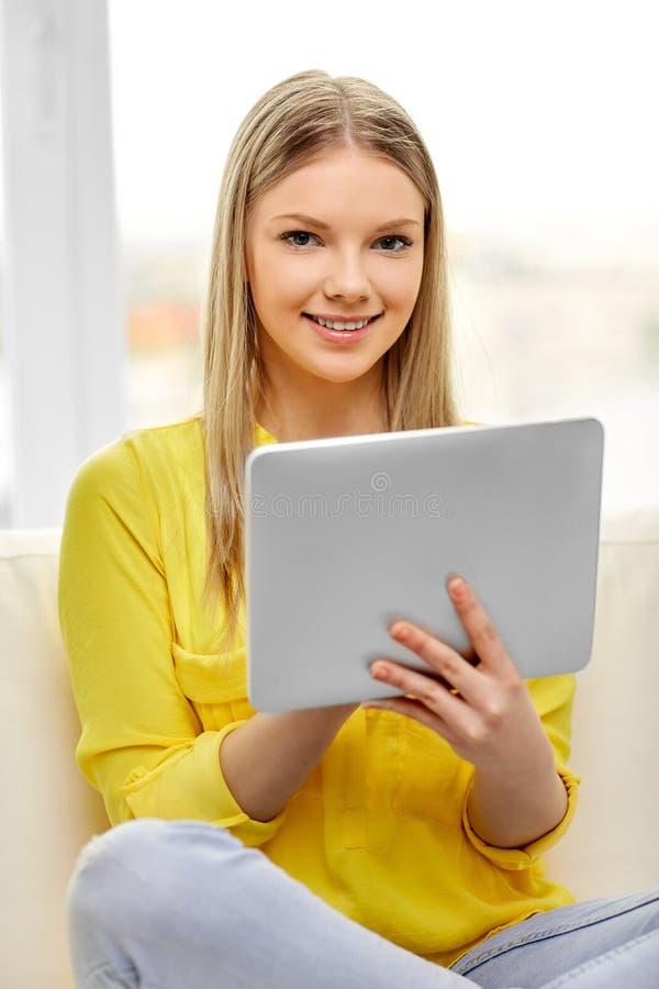 Молодая женщина или девочка-подросток с ПК планшета дома стоковое фото rf