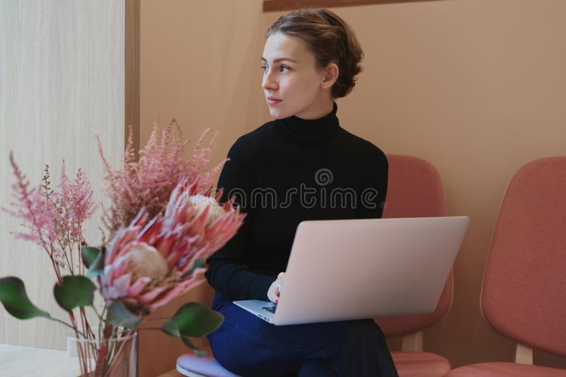 Молодая женщина или студент работая и писать используя ноутбук на коленях Сидящ в кафе около окна, романтичное настроение, теплый стоковая фотография rf