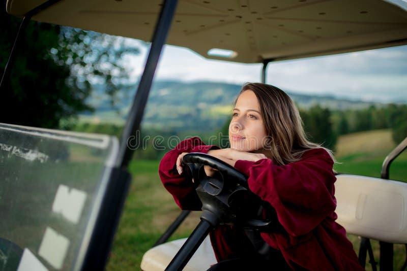 Молодая женщина имеет потеху с автомобилем гольфа дефектным на поле в горах стоковая фотография