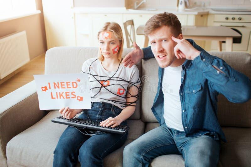 Молодая женщина имеет социальную наркоманию средств массовой информации Сидеть на софе бесчувственной Тело в оболочке со шнуром Р стоковая фотография