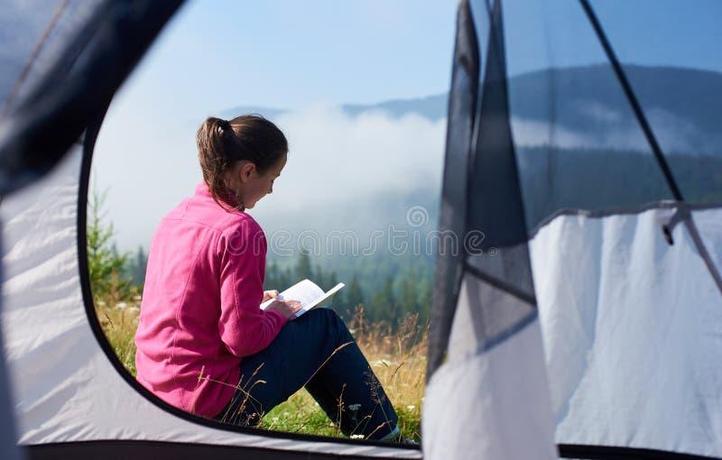 Молодая женщина имея остатки около туристского шатра в утре лета в горах стоковое изображение
