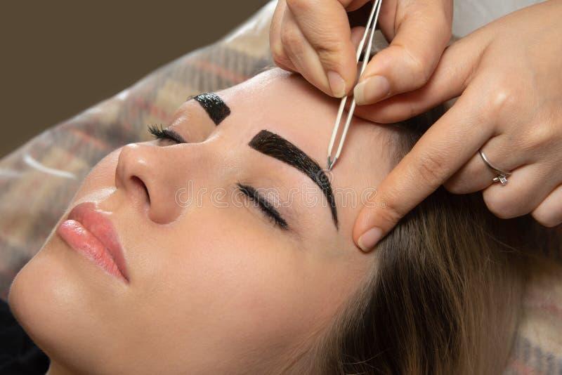 Молодая женщина имея профессиональную процедуру по коррекции брови в салоне красоты стоковое изображение rf