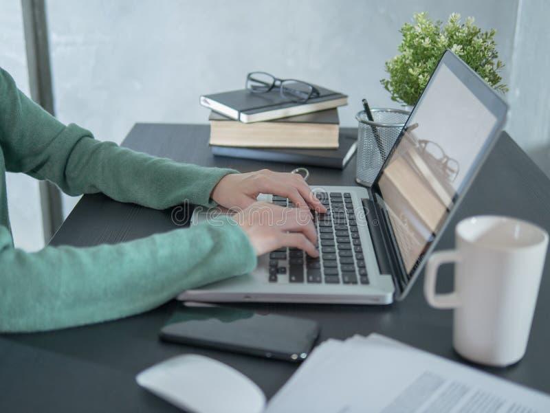 Молодая женщина использует ноутбук на черном столе дома стоковое фото rf
