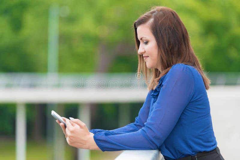 Молодая женщина используя ее смартфон стоковое фото rf