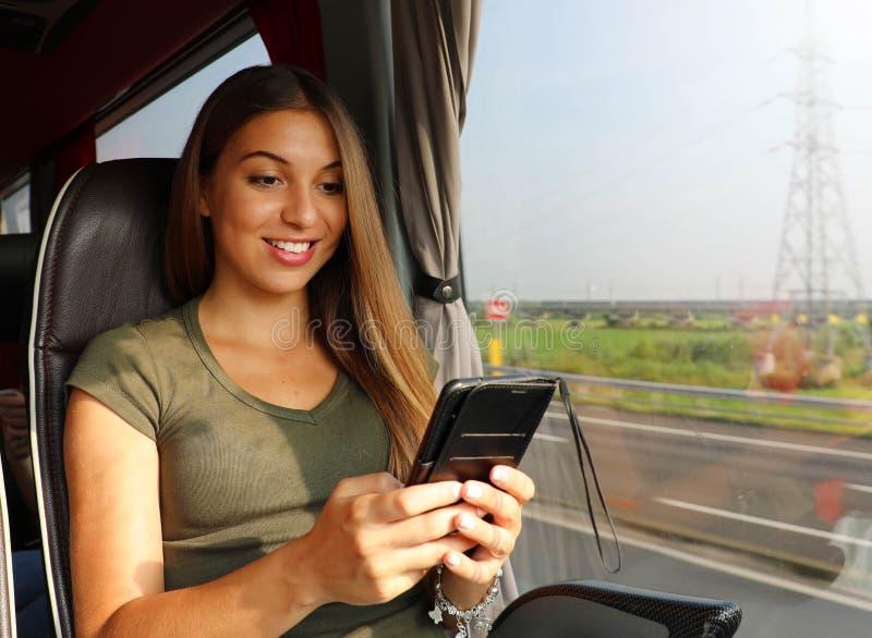 Молодая женщина используя ее смартфон на автобусе стоковые изображения rf