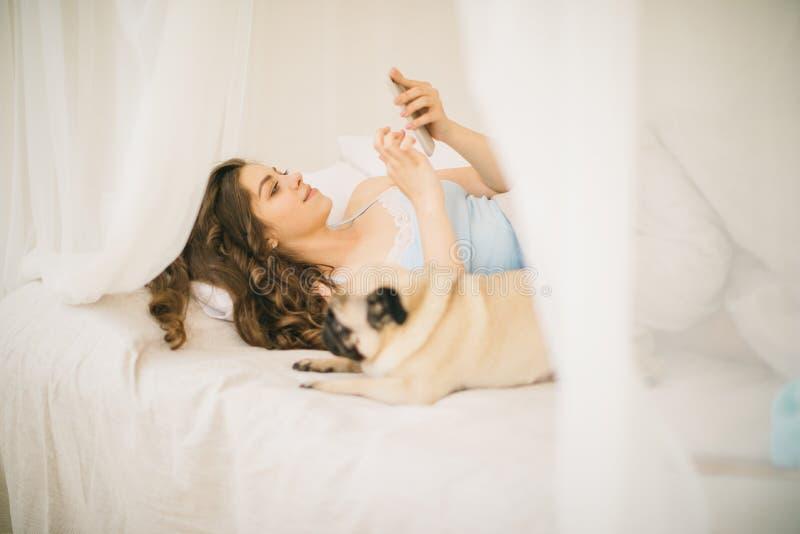 Молодая женщина используя мобильный телефон в кровати Малая собака мопса лежит рядом с ей стоковое фото rf