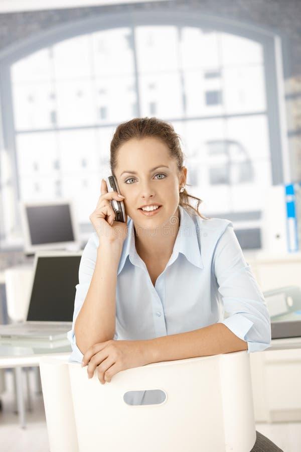 Молодая женщина используя передвижное усаживание в офисе стоковое изображение