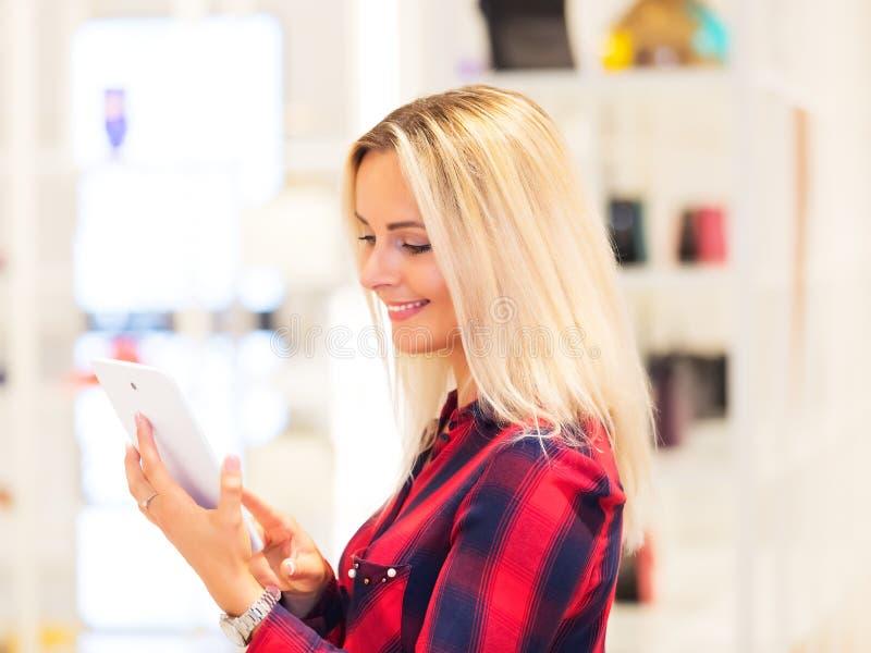 Молодая женщина используя планшет в магазине моды стоковое фото rf