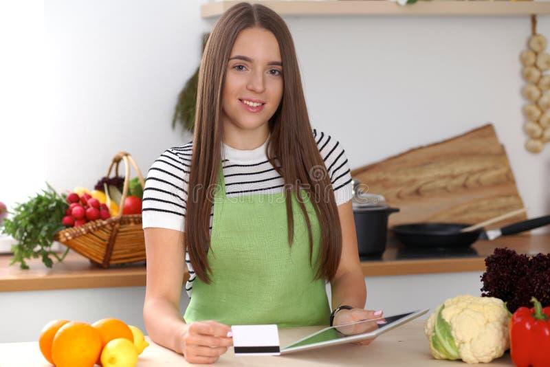 Молодая женщина используя планшет пока варящ в кухне Householding, вкусная еда и цифровая технология в образе жизни стоковые фото