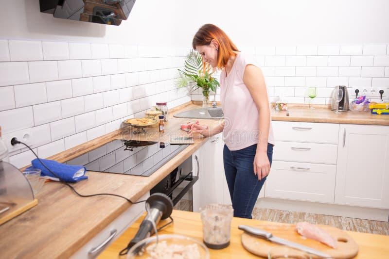 Молодая женщина используя смартфон полагаясь на кухне в современном доме телефонное сообщение чтения женщины женщина redhead печа стоковая фотография