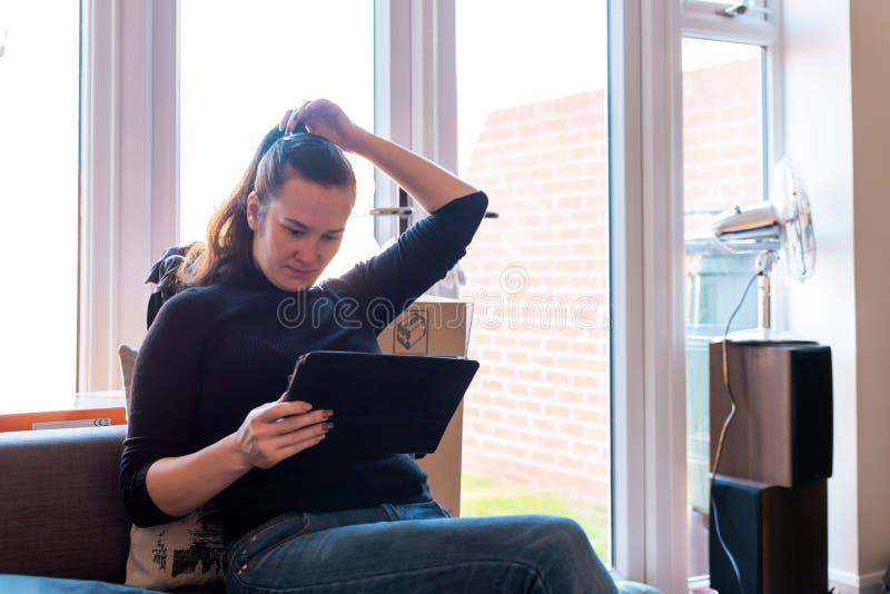 Молодая женщина используя таблетку на софе на новом доме рядом с дверью сада стоковое фото
