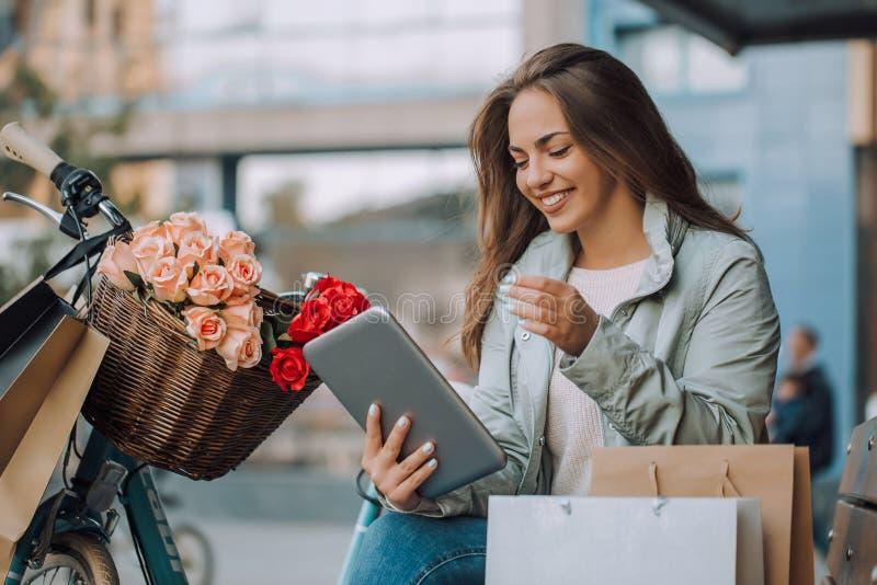 Молодая женщина используя цифровой планшет, после ходить по магазинам стоковые изображения