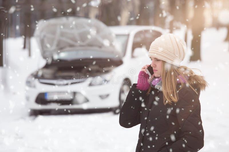 Молодая женщина используя smartphone для того чтобы вызвать помощь дороги Зима и стоковые фото